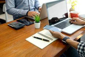två personer som arbetar på bärbara datorer på ett kontor foto
