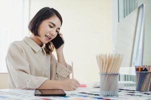 asiatisk kvinna designer talar i telefon foto