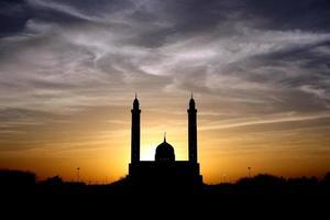 silhuett av moskén under molnig himmel foto