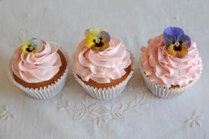 hemlagad rosa frosting vaniljmuffin med ätliga blommor foto