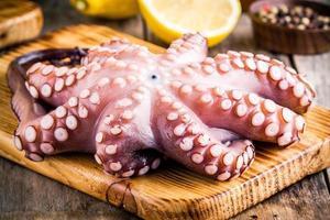 hela rå bläckfisk på skärbräda med citron och peppar foto