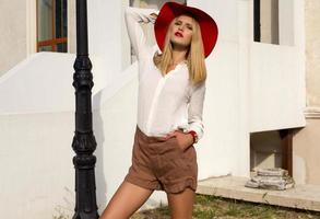 flicka med blont hår i elegant röd hatt och skjorta
