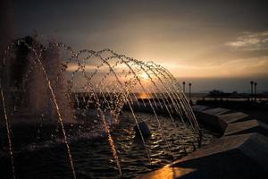 stadens fontän vid solnedgången. foto