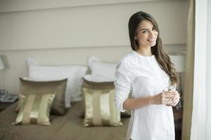 ung kvinna med ett glas vatten i rummet foto
