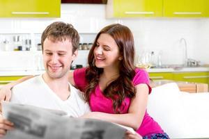 unga gifta par som sitter i soffan foto