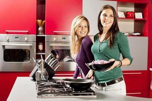 unga kvinnor i köket foto