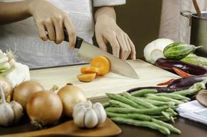 kvinna skär grönsaker foto