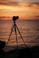 kamera och stativ i skymningen. foto