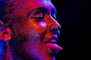 glitter makeup på en vacker kvinna ansikte på en svart bakgrund foto