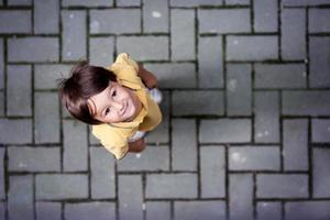 söt porträtt av liten pojke som står på gatan foto
