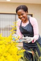 afrikansk kvinna som beskär växter i hennes trädgård foto