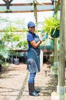 afrikansk trädgårdsmästare som arbetar i växthus foto