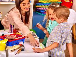 barn med lärarkvinnan som målar på papper i dagis foto