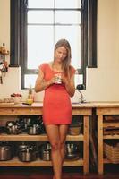 kaukasisk kvinna med kopp kaffe i sitt kök foto