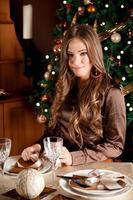 vacker ung kvinna som ställer in chrtismas-bordet foto