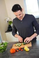 stilig ung man kök förbereder organiska grönsaker sallad sommarlunch foto