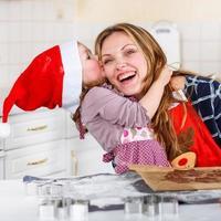 mamma och lilla barnflickan bakar pepparkakakakor för christ foto