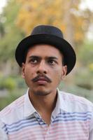 ung man som bär svart hatt foto