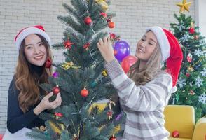 två kvinnor som dekorerar julgranen foto