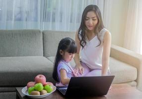 mor och dotter använder en bärbar dator