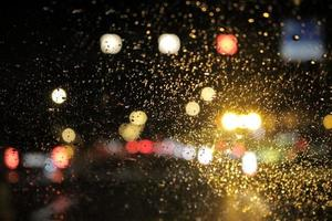 regndroppar på vindrutan på natten foto