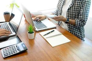 yrkesverksamma som arbetar med bärbara datorer vid ett skrivbord foto