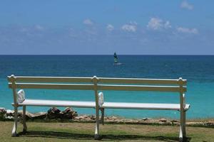 vit bänk framför havet foto