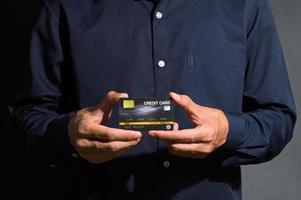närbild av en affärsman som innehar ett kreditkort foto