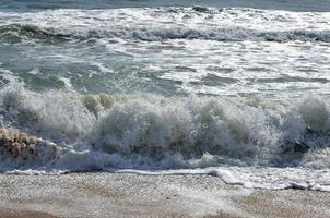 havsvågor som kraschar vid stranden foto