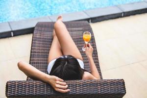 lycklig vacker kvinna som kopplar av nära lyxig pool foto