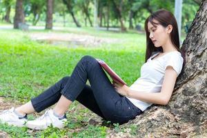 asiatisk kvinna som läser en bok i parken