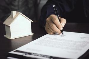 närbild av en person som tecknar ett fastighetskontrakt foto