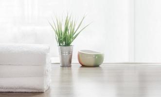 vikta vita handdukar och krukväxt på träbord foto