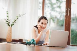 kvinna med hantlar på bärbara datorn