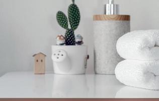 bunt med vikta handdukar och en växt på ett vitt bord