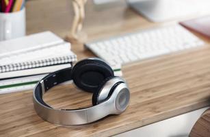 närbild av hörlurar på ett träskrivbord foto