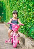 flicka som cyklar på en rosa cykel foto
