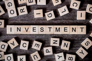 närbild av träbokstäver som stavar ut ordet investering foto