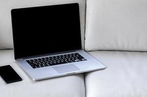 bärbar dator mockup med en smartphone på en soffa