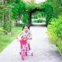 flicka som cyklar i en park foto