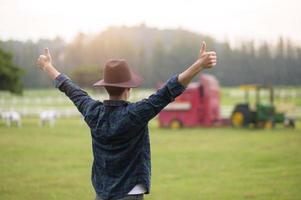 ung jordbrukare med tummen upp foto