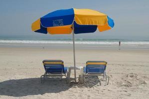 strandstolar och paraply foto