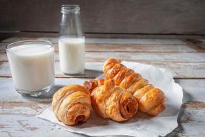 färska bröd rullar med ett glas mjölk foto