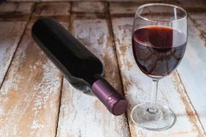 vinglas och vinflaska på träbord