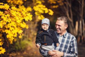 farfar håller sitt barnbarn på armen, höst foto