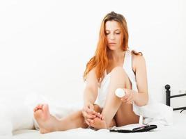 kvinna som tar hand om fötter med kosmetisk kräm foto
