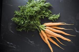 organiska morötter på svart bakgrund foto