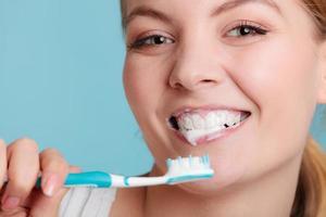 kvinna med tandborste som borstar rengöringständer foto