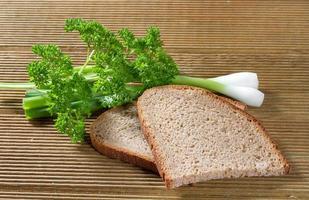 svart bröd med gröna lökar foto