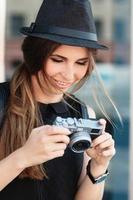 de leende studentfotograferar med digital spegelfri kamera. foto